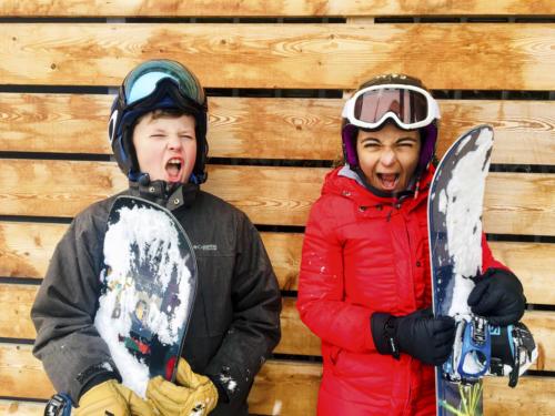 Kids smiling on snowboard
